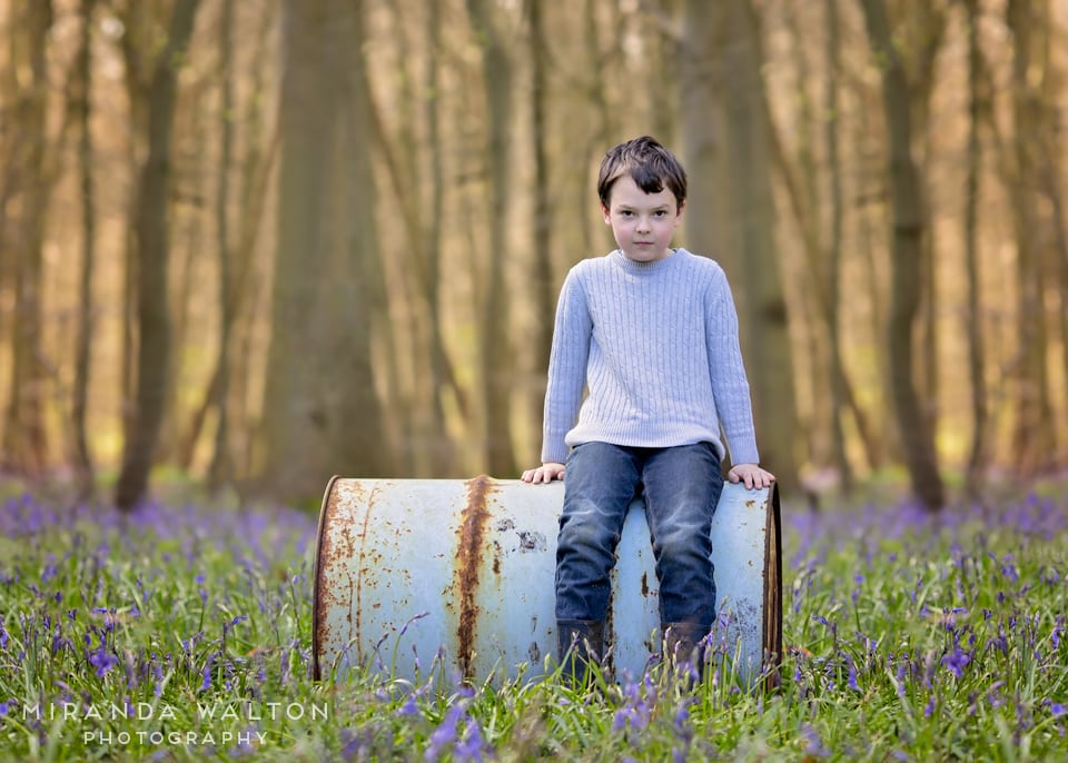 boy sitting on barrel in the bluebells