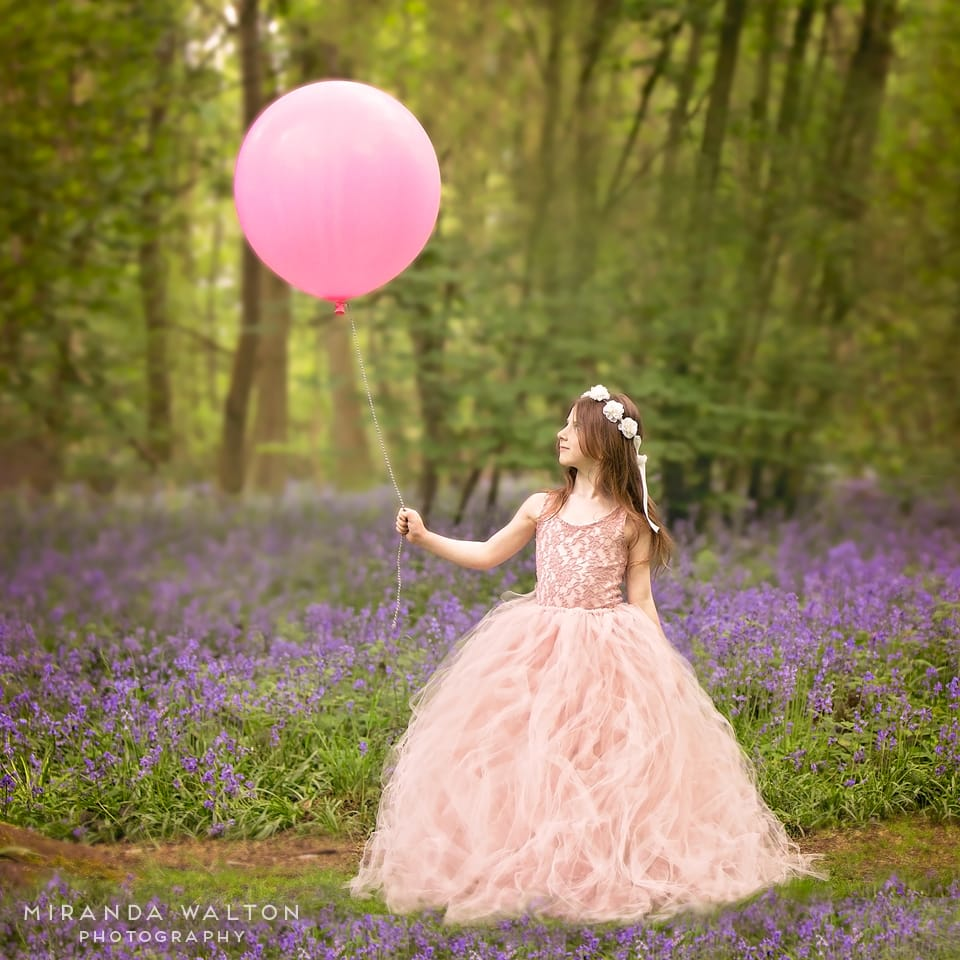 girl with balloon in bluebells