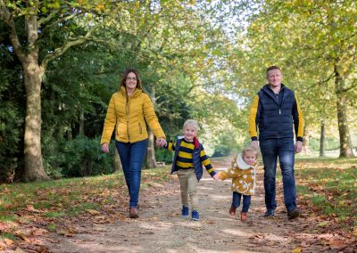 Family of four all wearing coordination mustard and navy clothing walking towards the camera for Northampton family photography session
