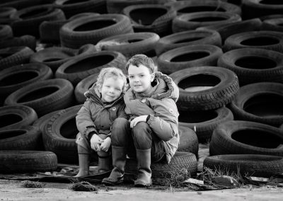 Brothers sitting on a pile of tyres