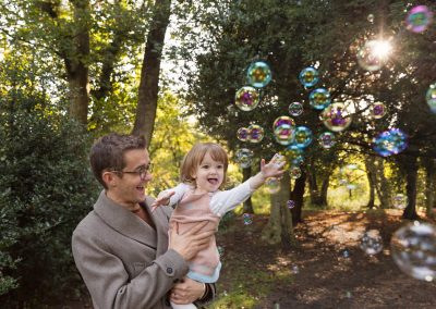 Dad holding girl in Northampton family photography session reaching out for bubbles in the sun