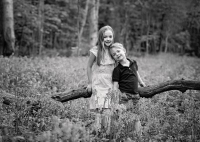 Siblings looking at camera in Bluebell wood Northampton