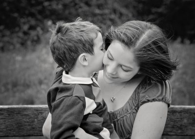 Young boy kissing his mother's cheek by family photographer
