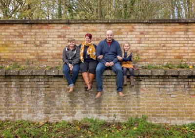 Family of four sitting on wall on Northampton photoshoot
