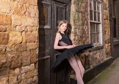 Ballet dancer in black tutu leaning against old door on Northampton photoshoot