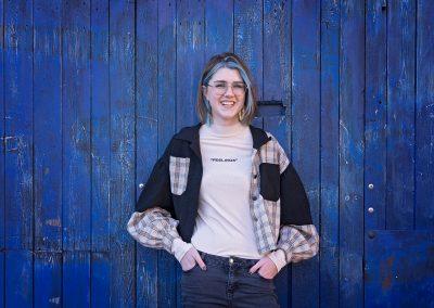 Teenage girl laughing leaning against blue door