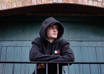 Teenage boy wearing black hoodie and cap in front of green doors at Audio Works Northampton
