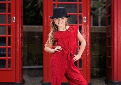 Young girl with long blonde hair wearing red jumpsuit and black hat in front of red Northampton phone box