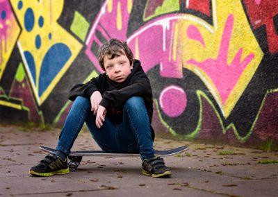 Boy sitting on skateboard in front of graffiti wall on Northampton photoshoot